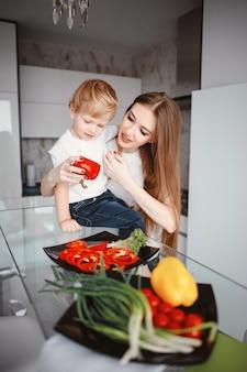 Familia prepara la ensalada en la cocina.