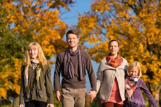 Familia que camina delante de árboles coloridos en otoño