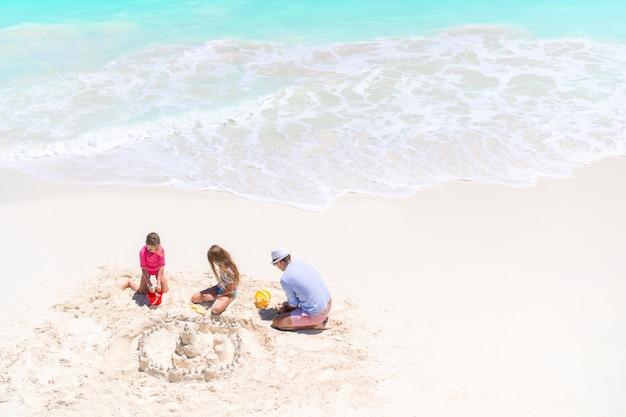 Familia que hace el castillo de la arena en la playa blanca tropical. vista superior