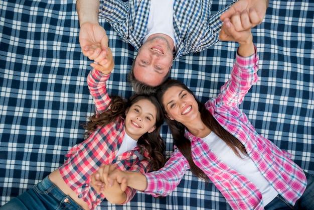 Familia que miente en la manta a cuadros azul que lleva a cabo sus manos en jardín
