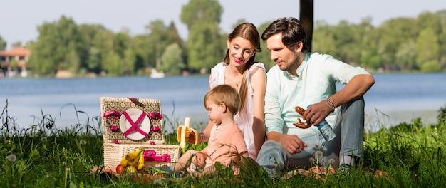 Familia que tiene comida campestre en el lago que se sienta en prado