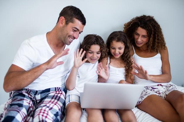Familia que tiene video chat en la computadora portátil