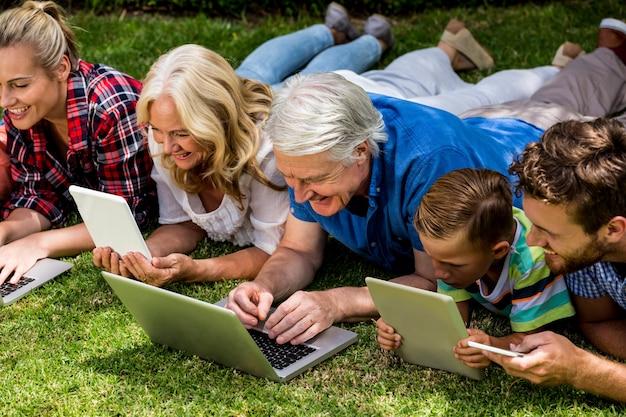 Familia que usa tecnologías mientras se relaja en el parque