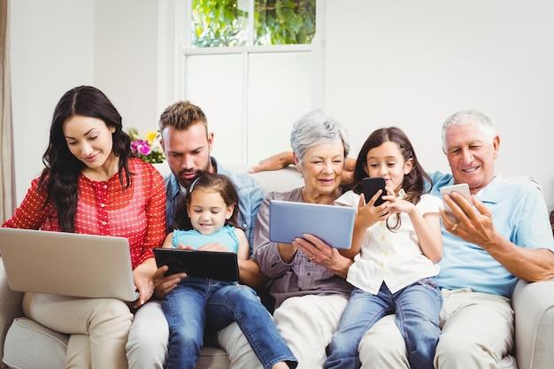 Familia que usa tecnologías mientras está sentado en el sofá