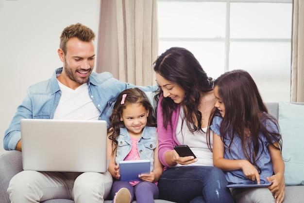Familia que usa tecnologías modernas en el sofá