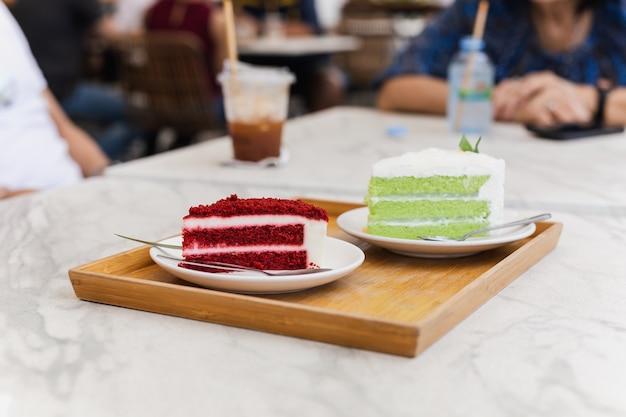 Familia con una rebanada de pastel de terciopelo rojo y pastel de té verde en el café