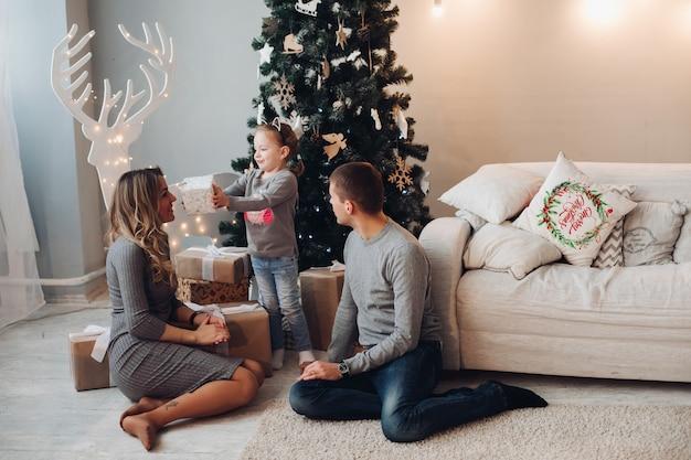 Familia con regalos para navidad. árbol de navidad.