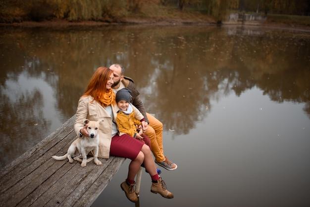 Familia relajante en el interior y acariciando perro mascota