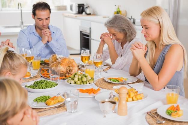 Familia rezando antes de la cena