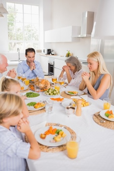 Familia rezando antes de comer