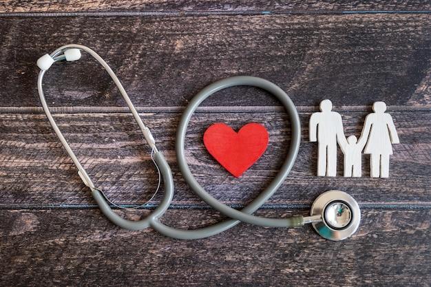 Familia roja del corazón, del estetoscopio y del icono en el escritorio de madera. concepto de seguro médico