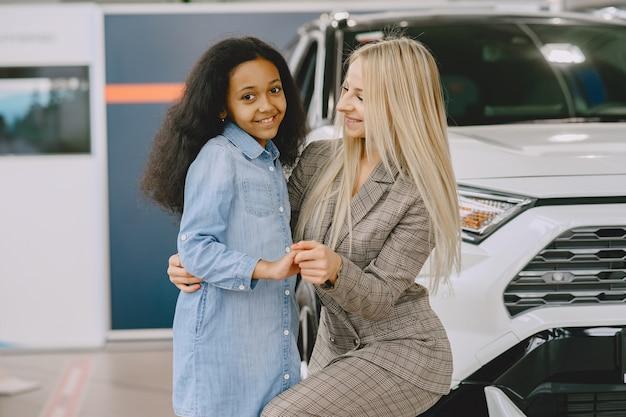 Familia en un salón de autos. mujer comprando el coche. niña africana con mther.