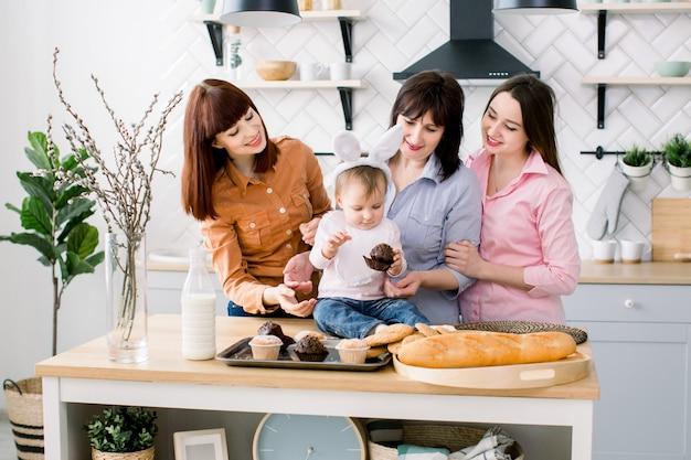 Familia satisfecha con la abuela, dos hijas y una pequeña niña disfrutando del pasatiempo en pascua y comiendo pastelitos. una niña tiene orejas de conejo en la cabeza.