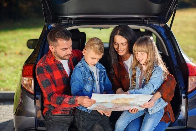 Familia satisfecha de padre guapo, madre bonita y niños encantadores en vacaciones familiares conjuntas