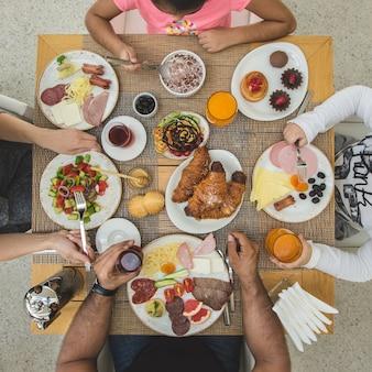 Familia sentada alrededor de la mesa de desayuno y comiendo