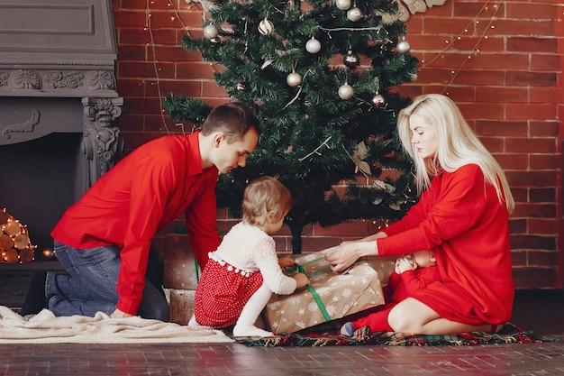 Familia sentada en casa cerca del árbol de navidad