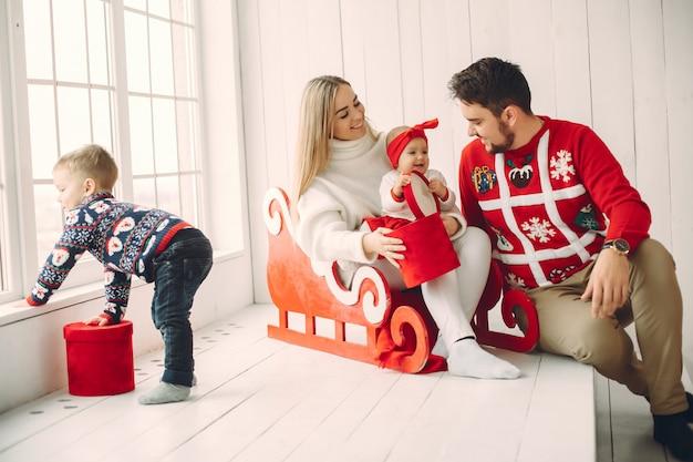 Familia sentada en casa con regalos de navidad