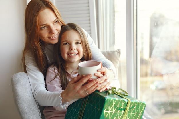 Familia sentada en casa con regalos