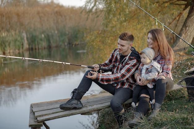 Familia sentada cerca del río en una mañana de pesca