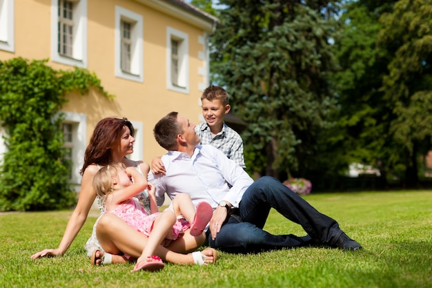 Familia sentada en el césped frente a su casa