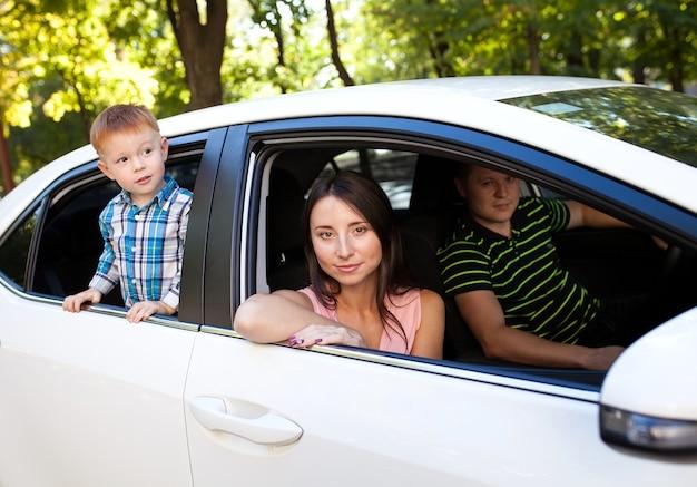 Familia sentada en el coche mirando por las ventanas