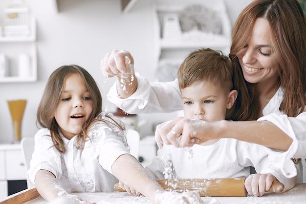 Familia sentada en una cocina y cocinar la masa para pastel
