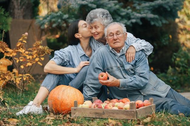 Familia sentada en un jardín con manzanas y calabaza