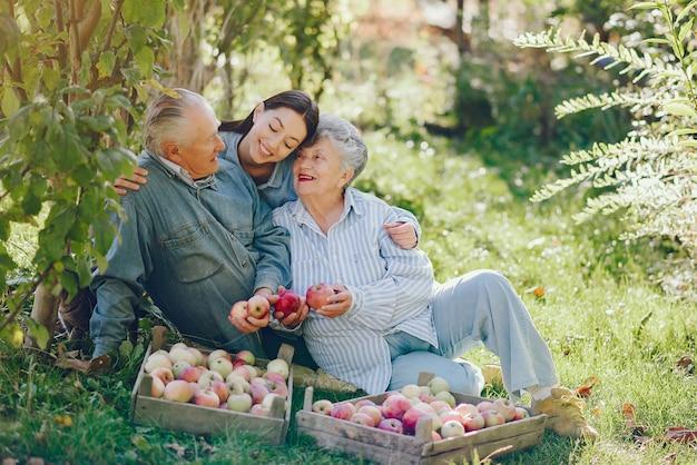 Familia sentada en un jardín con manzanas