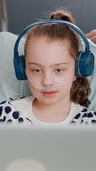 Familia sentada junto a la hija mientras juega videojuegos en línea con un ordenador portátil en la sala del hospital