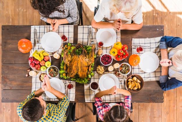 Familia sentada a la mesa y rezando