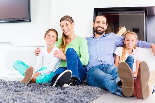 Familia sentada en el piso de la sala, chimenea.