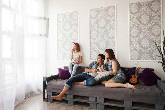Familia sentada en el sofá y comiendo fresas en casa