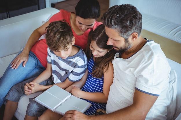 Familia sentada en el sofá y mirando un álbum de fotos