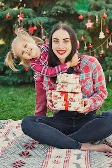 Familia sesión de fotos de año nuevo de madre e hija en julio cerca del árbol de navidad con regalos en el parque