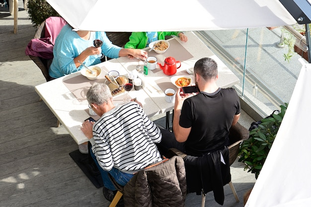 La familia se sienta en un café a la mesa y come.