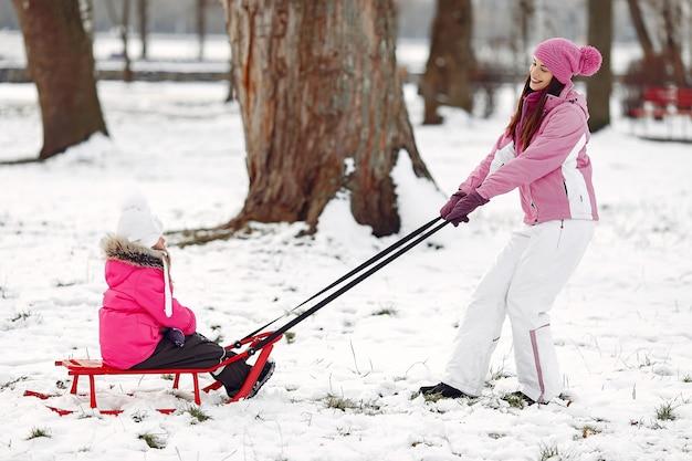 Familia con sombreros de invierno tejidos en vacaciones familiares de navidad. mujer y niña en un parque. gente jugando con trineo.