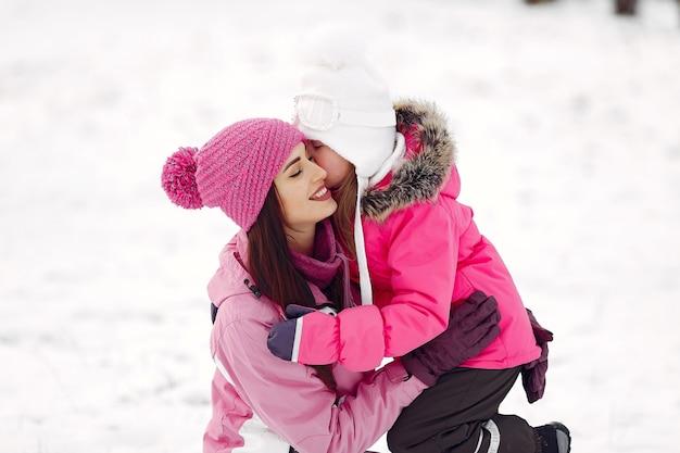 Familia con sombreros de invierno tejidos en vacaciones familiares de navidad. mujer y niña en un parque. gente jugando.