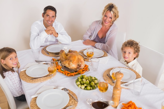 Familia sonriendo alrededor de una cena de asado