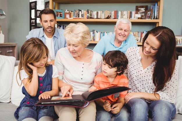 Familia sonriente con abuelos con álbum de fotos