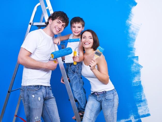 Familia sonriente amable con hijo joven pintando la pared
