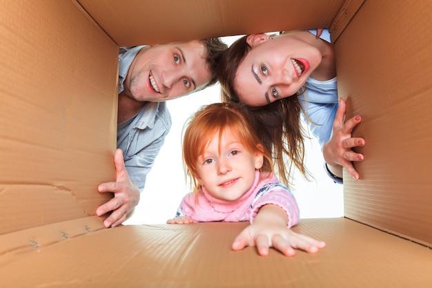 La familia sonriente en una caja de cartón lista para mudarse