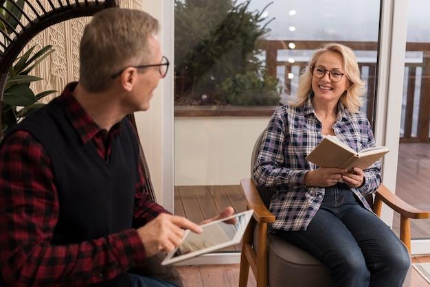 Familia sonriente en casa leyendo y mirando la tableta