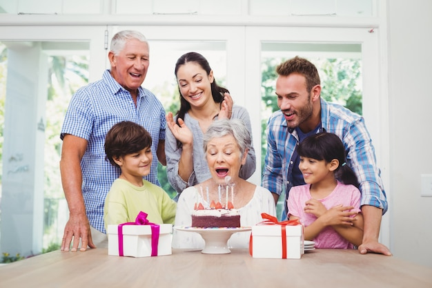 Familia sonriente celebrando la fiesta de cumpleaños de la abuela