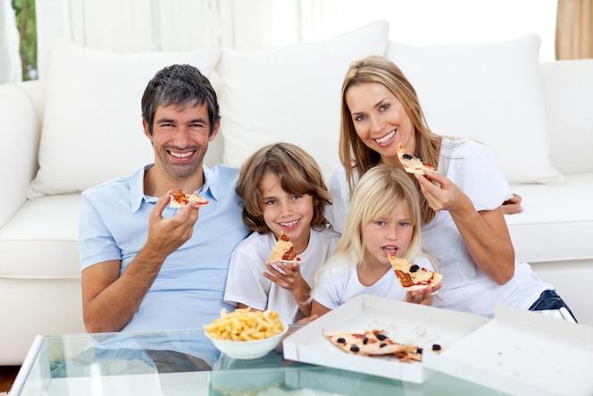 Familia sonriente comiendo una pizza sentado en el piso