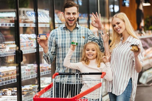 Familia sonriente eligiendo comestibles y mostrando gesto bien