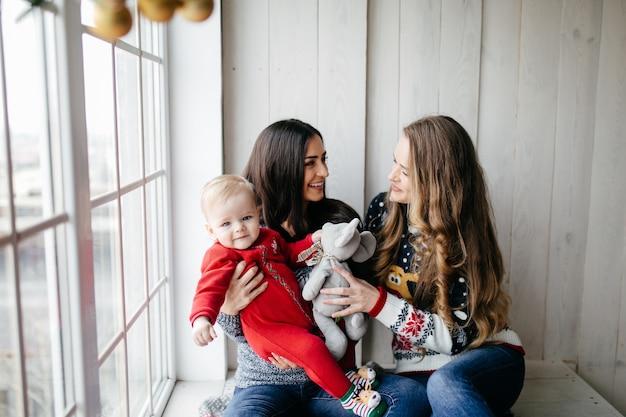Familia sonriente feliz en el estudio en el fondo del árbol de navidad con el regalo