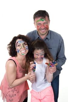 Familia sonriente y feliz con pintacaritas, padres e hija