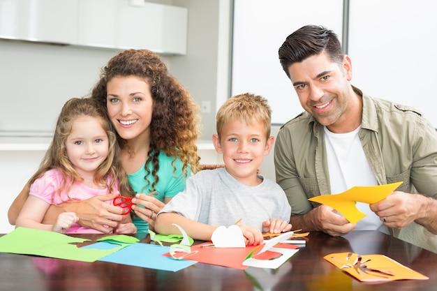 Familia sonriente haciendo manualidades en la mesa