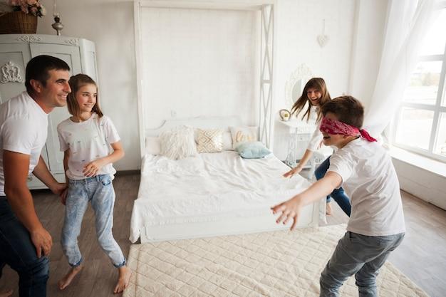 Familia sonriente jugando aficionado ciego en dormitorio