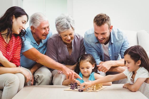 Familia sonriente jugando al ajedrez